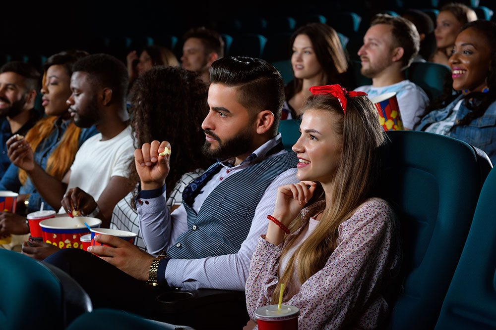 Catching up the latest hits. Shot of young people watching a movie at the cinema